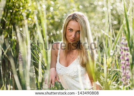 Blond young woman in a grass close-up. - stock photo