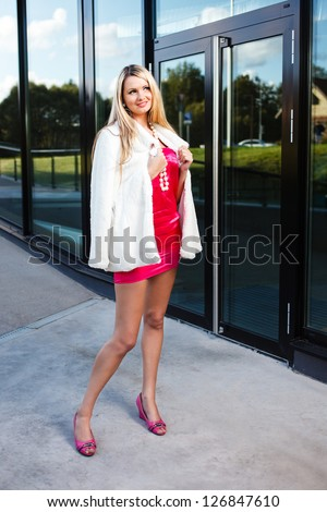 Blond young woman in pink dress and white fur coat posing near a modern building. - stock photo