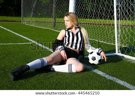 Blond young woman in soccer suit play on the field with black and white ball