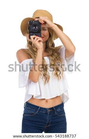 Blond young woman in straw hat, jeans and white shirt talking a photo. Front view. Three quarter length studio shot isolated on white.