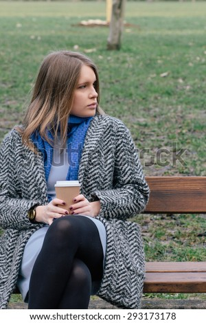 Blond young woman on a bench in a park, holding a cup of warm drink.