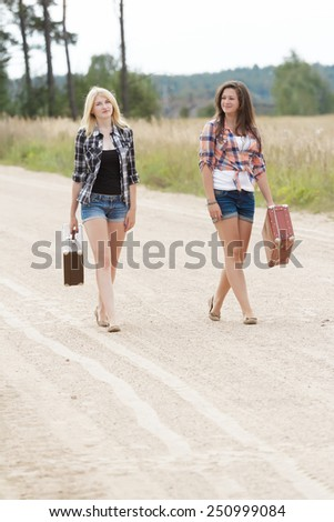 Blonde and brunette friends walking on a country road - stock photo