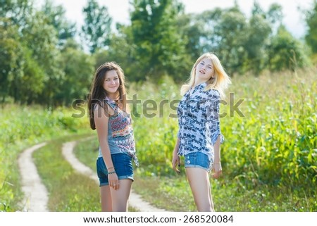 Blonde and brunette girls are standing on the country dirt road on farm outback vacations - stock photo