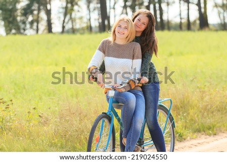 Blonde and brunette girls during cycling on dirt road - stock photo
