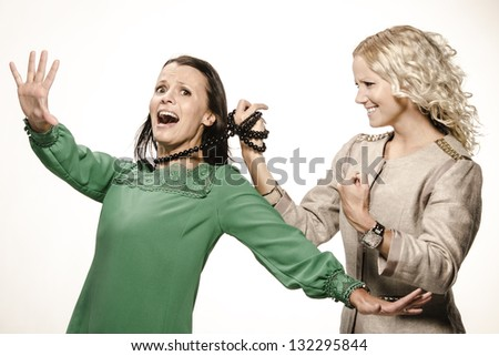 Blonde and brunette woman fighting. Friends having fun. - stock photo