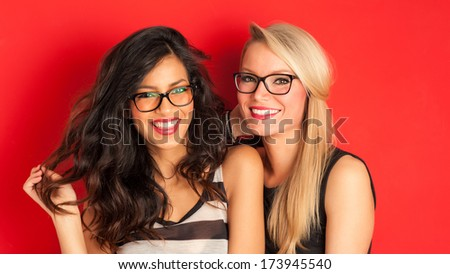 Blonde and brunette women having fun portrait against red background.  - stock photo