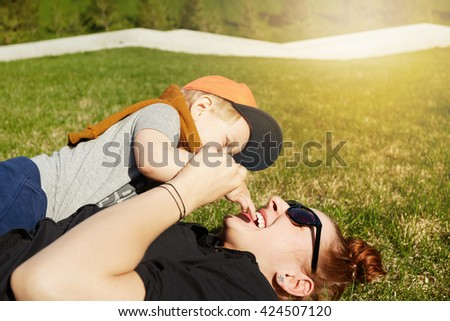 Blonde baby boy having fun with his redhead mother in sunglasses, sitting on her and playing with her face. Beautiful young female and son playing in the park on sunny day. Love and hapiness concept.  - stock photo