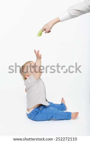 blonde baby boy playing with a toy held by adult - stock photo