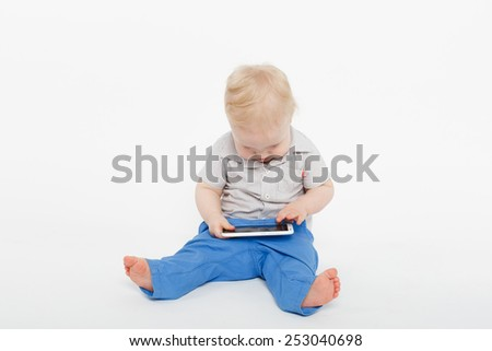 blonde baby boy sitting with a mobile phone over white background - stock photo