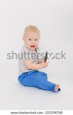 blonde baby boy sitting with a mobile phone over white background