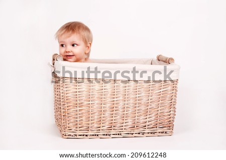 blonde baby sitting at the basket on white background