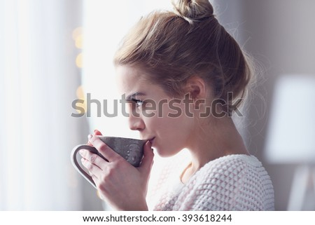 Blonde beautiful  girl looking in the window and holding a cup of coffee or tea in her hands - stock photo
