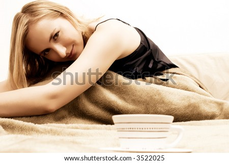 Blonde beautiful girl sitting on the bed in the morning
