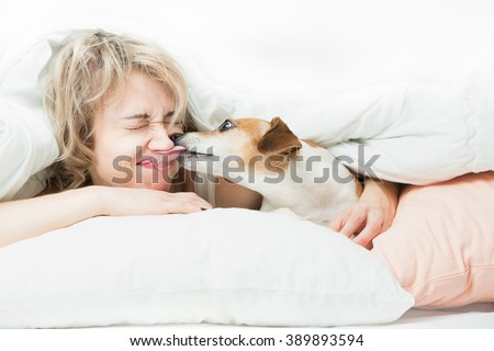 Blonde beautiful Woman and dog playfully indulge in fun on the bed. Dog bites the girl's nose. Happy time with pets - stock photo