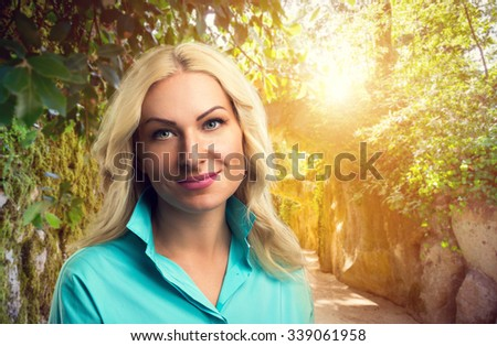 Blonde beautiful woman in the park on sunny day - stock photo