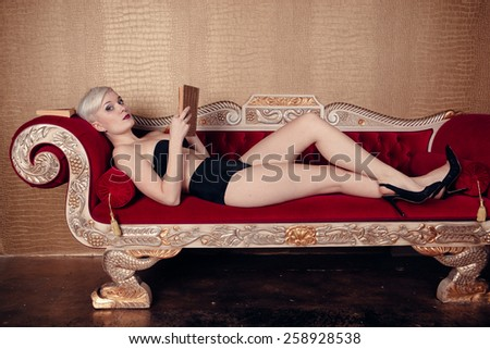 Blonde beautiful woman on red sofa wearing black bra. Cabaret style