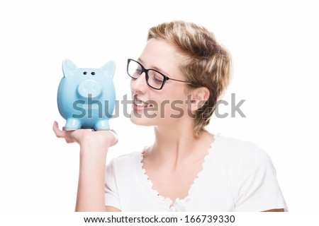 blonde beautiful woman smiling at her blue piggy bank on white background - stock photo