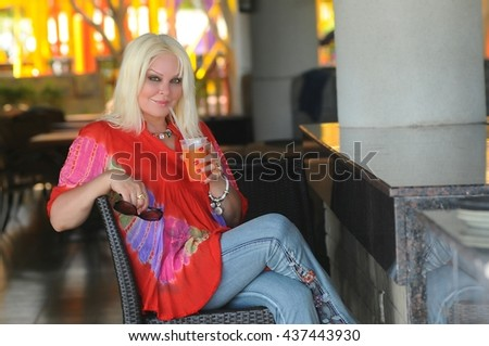 Blonde beautiful woman with nice smile and with cocktail  in summer beach cafe,  - stock photo