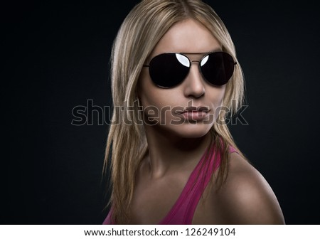 Blonde beautiful woman with sunglasses over dark concrete background with copy space