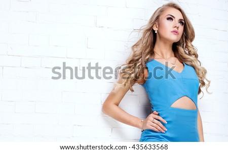 Blonde beautiful young woman posing in blue dress. Glamour makeup. Long hair. Studio shot.  - stock photo