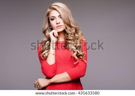 Blonde beautiful young woman posing in red dress. Glamour makeup. Long hair. Studio shot. - stock photo
