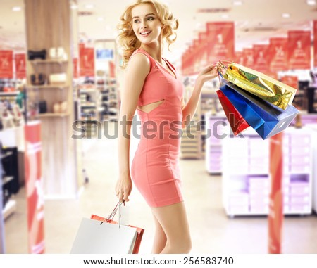 Blonde beauty holding shopping bags - stock photo