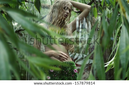 Blonde beauty in tropical forest - stock photo