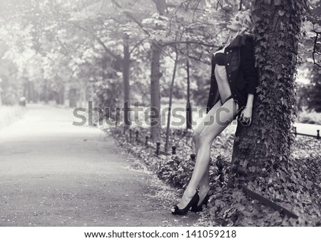 Blonde beauty posing in park - stock photo