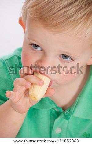 Blonde blue eyed baby boy wearing a green polo shirt sitting eating a ripe banana and enjoying his healthy food - stock photo