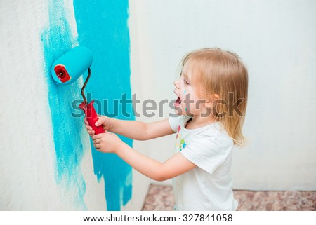 blonde blue-eyed little girl three years doing repairs in the apartment, fun paints the wall by roller / brush in blue - stock photo