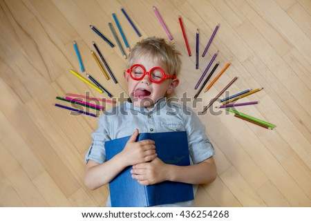 blonde boy in red shirt in glasses with a book lying on the floor next to the colored pencils and grimaces - stock photo