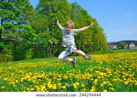 blonde boy jumping on a meadow - stock photo