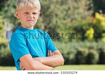 Blonde boy looking angry and frowning at camera in the park - stock photo