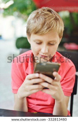 blonde boy playing phone in outdoor cafe