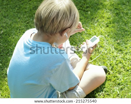 Blonde boy sitting on grass, listening to MP3 player, rear view, elevated view - stock photo