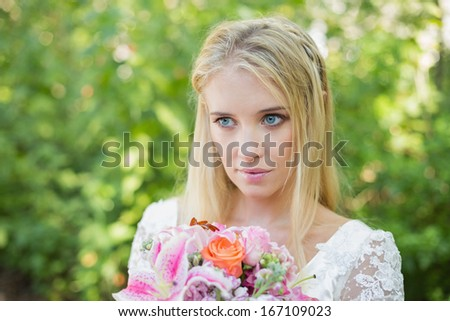 Blonde bride holding colorful bouquet looking away in the countryside