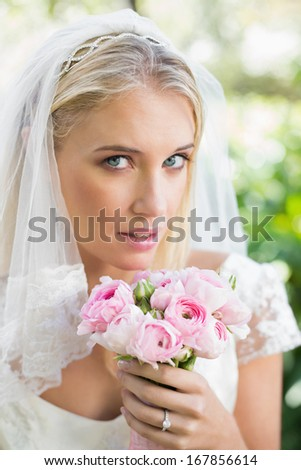 Blonde bride in a veil holding her rose bouquet in the countryside