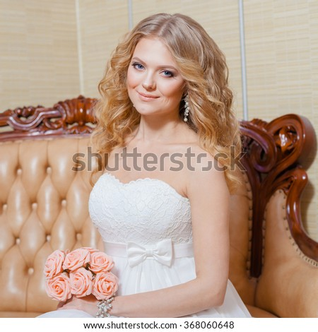 blonde bride in vintage interior. The beautiful woman posing in a wedding dress - stock photo