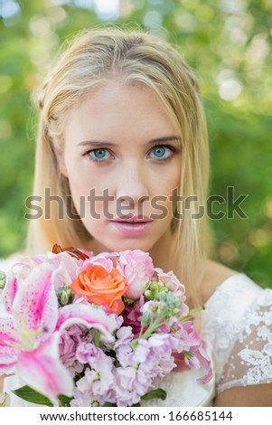 Blonde bride looking at camera holding bouquet in the countryside