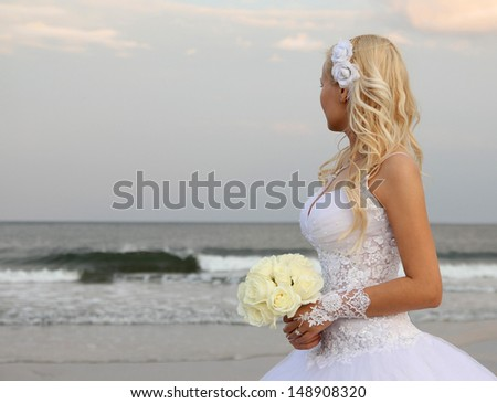 Blonde bride walking on the the beach. beautiful young woman in wedding dress looking on the ocean - stock photo
