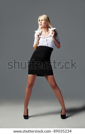 Blonde business, fashion girl posing in a white shirt, black mini dress and white glasses - stock photo