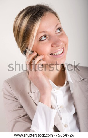 blonde business woman in beige suit jacket talking on cell phone