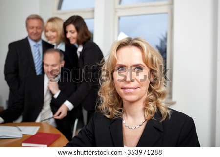Blonde business woman with team in the background