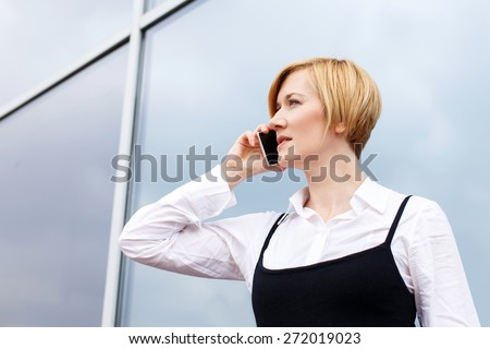 Blonde businesswoman calling by smartphone at business center