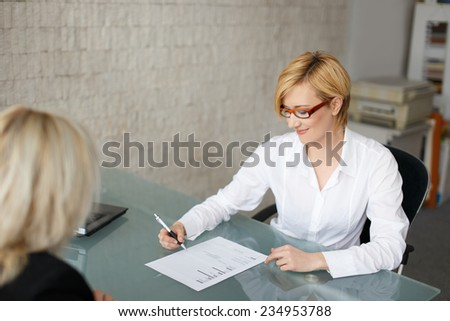 Blonde businesswoman fill out a form in office - stock photo