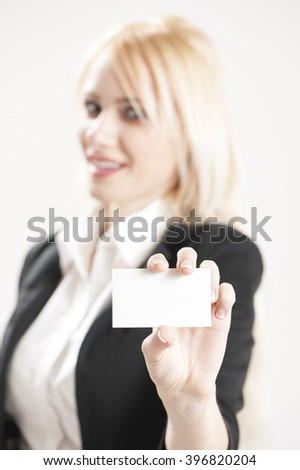Blonde businesswoman holding a blank business card. Selective focus on blank business card - stock photo