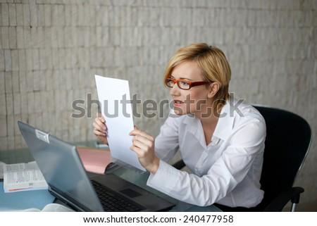 Blonde businesswoman in glasses reading letter, bad news - stock photo