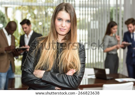 Blonde businesswoman leader looking at camera with arms crossed in working environment. Group of people in the background