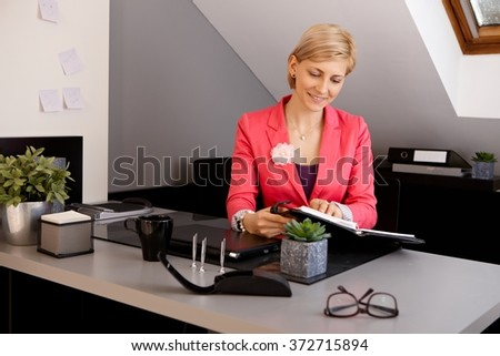 Blonde businesswoman looking at organizer, sitting at desk in office.