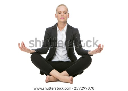 blonde businesswoman seated on the floor doing a yoga position with her eyes closed